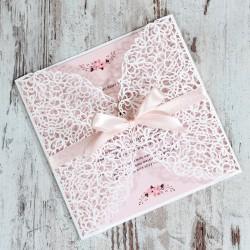 Białe, ażurowe zaproszenia ślubne z różową wstążką